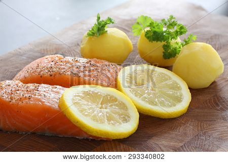 Salmon Fillet With Potatoes, Lemon Slices And Parsley Served On A Wooden Board. Close Up Stock Photo
