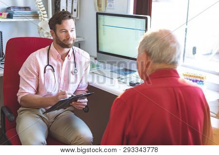 High angle view of a Caucasian male doctor talking to Caucasian senior patient while holding medical report in clinic