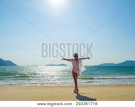 Woman enjoying her holidays at the tropical beach wearing a white summer top