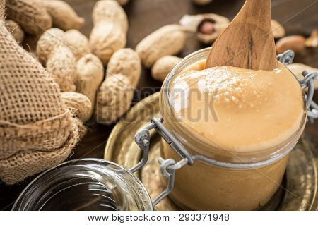 Organic Peanut Butter In Glass Jar With Peanuts In Shell On Wooden Background. Healthy Breakfast Veg