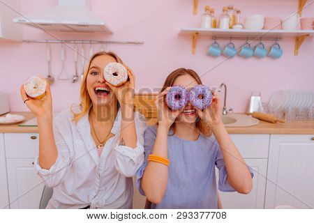 Sisters Having Fun Showing Sweet Doughnuts In The Kitchen