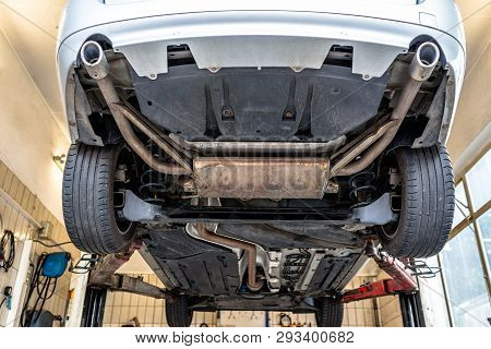 Car chassis on the lift, view from the bottom. Visible exhaust system, wheels, brake hoses. poster