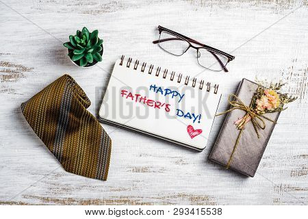 Happy Father's Day Concept. Flat Lay Image Of Gift Box, Necktie, Glasses And Notebook With Happy Fat