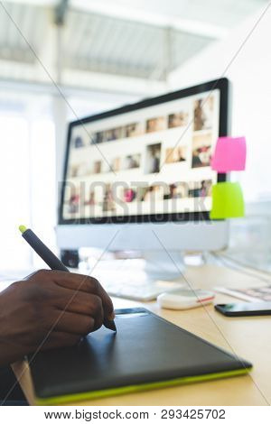 Close-up young African-American graphic designer working on graphic tablet and computer at desk in office