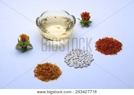 Flowering And Saffron Flowers. Seeds For Home Garden. Spices And Cosmetic Oil From Safflower On A Wh