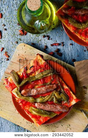 high angle view of a slice of coca de recapte, typical catalan savory cake similar to pizza, made with grilled eggplant and red pepper, and sausages, on a wooden table next to a cruet with olive oil