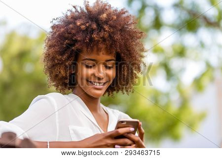 Outdoor Portrait Of A Young Black African American Young Woman Texting  On Mobile Phone