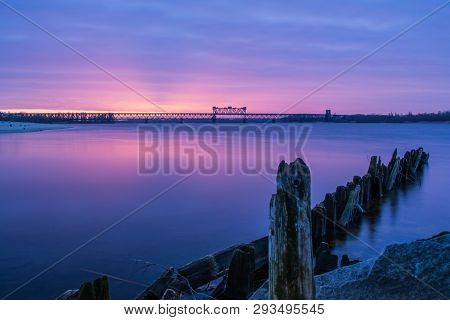 Sunrise Over Bridge. Dawn On The Coast. Early Morning On The Shore. Dramatic Purple Color Over River