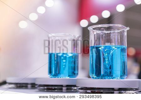 Close Up Of Beautiful Vortex Blue Colorful Chemistry Liquid In Beaker Laboratory Flask On Magnetic S