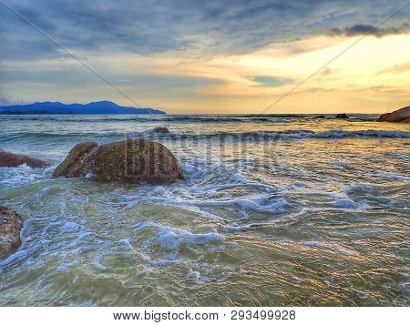 A Beautiful Sunset View On The Sea Shore With The Water Slash On The Shore Beach.