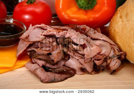 Makings of a roast beef sandwich including California Sourdough deli sliced angus roast beef tomato cheddar cheese Au Ju Sauce peppers poster