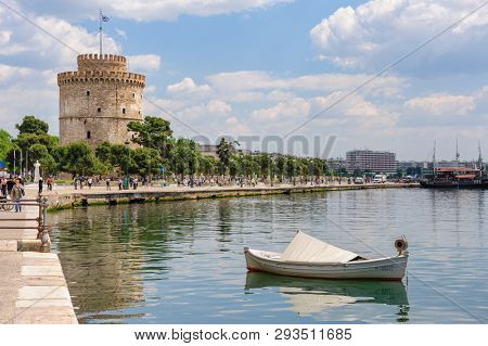 Thesalloniki, Macedonia, Greece - 12th May 2015: People walking and relaxing at embankment near white Tower, Thessaloniki, Greece. This tower is a monument and museum on the waterfront of the city.