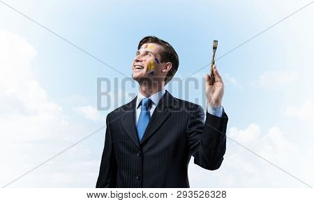 Horizontal Shot Of Young And Happy Businessman In Black Suit Holding Paintbrush In His Hand While St
