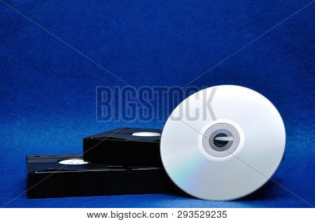 Two Video Cassettes Isolated On A Blue Background With A Cd