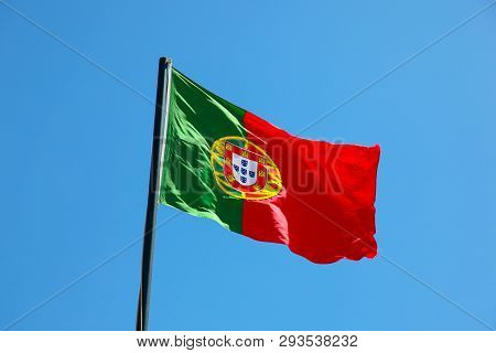 National Flag Of Portugal Blowing In The Wind On Flag Pole With Blue Sky Background. Portugal