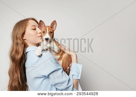 Cute Young Woman Hugging And Kissing Her Puppy Basenji Dog. Love Between Dog And Owner. Isolated On