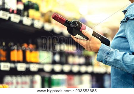 Alcohol Shelf In Liquor Store Or Supermarket. Woman Buying A Bottle Of Red Wine And Looking At Alcoh