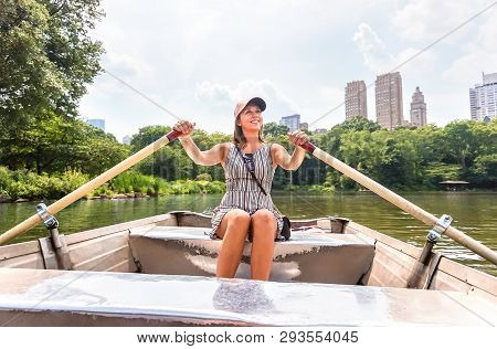 Woman Rowing A Rowboat And Having Fun In Nature. Boating In Summer. Smiling Happy Lady Enjoying Outd