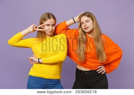 Two Stunning Young Blonde Twins Sisters Girls In Colorful Clothes Looking Camera, Showing Victory Si