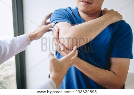 Doctor Physiotherapist Assisting A Male Patient While Giving Exercising Treatment Massaging The Arm