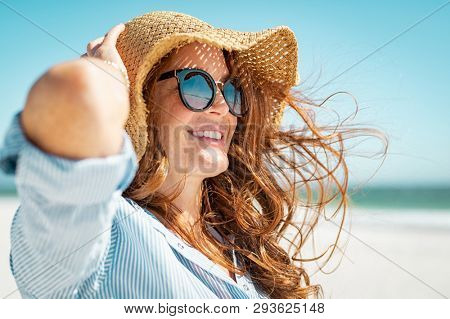 Side view of beautiful mature woman wearing sunglasses at beach. Young smiling woman on vacation looking away while enjoying sea breeze wearing straw hat. Closeup portrait of attractive girl relaxing.