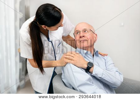 Smiling Nurse And Old Senior Man Patient At Home. Care For Older People Concept