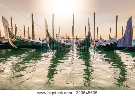 Gondolas Lay Dormant Waiting For Tourists, At Sunset With Long Shadows, And The Church Of Santa Mari