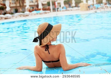 Young Woman Sitting Near The Pool. Sexy Girl With Healthy Tanned Skin. Female With Sun Hat Relaxing