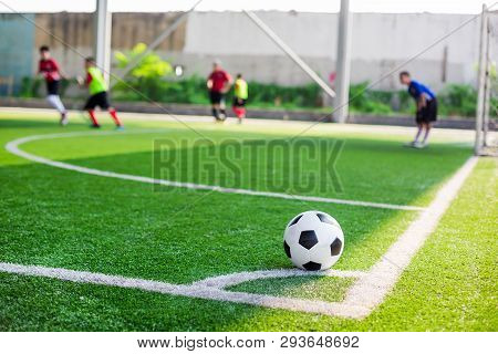 Soccer Ball On Green Artificial Turf At Corner Of Football Field With Blurry Players Background