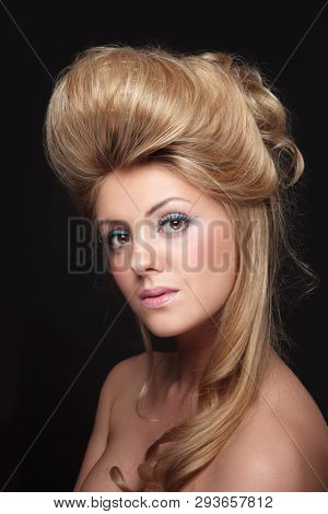 Young beautiful woman with vintage style prom hairdo and fancy makeup