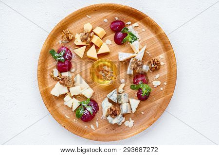 Cheese Plate Served With Grapes, Honey And Nuts. Camembert, Parmesan, Dorblu And Maasdam Served On W