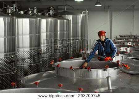 October 10, 2011. Purcari Winery, Stefan Voda - Moldova. A Woman Pours Red Wine Into Large Metal Bar