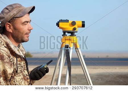 Worker With Level, Surveyor Builder With Geodesy Equipment Close To Highway, With Mobile Phone, Smil