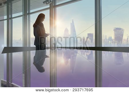 Young Woman Standing Next To The Office Window With Beautiful City Of London View And Reading Messag