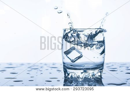 Water Splash In A Glass With A Piece Of Ice On A White Background, A Piece Of Ice Falling Into Glass