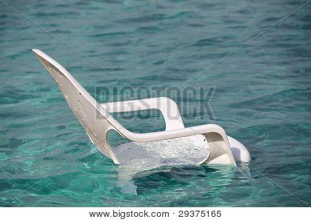 White Plastic Beach Chair In Sea