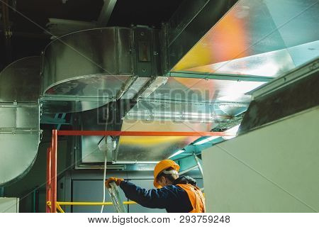 Young Man In Orange Work Vest, Safety Belt And Hard Hat Going To Repair Hvac System. Toned Photograp