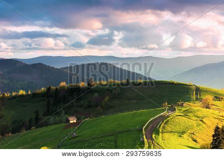 Mountainous Countryside In Evening Light. Grassy Rural Fields On Rolling Hills. Wooden Fence Along T