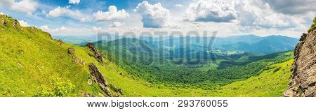 Panorama Of A Valley In Summer. Beautiful Landscape With Rocks On Grassy Hills. Distant Ridge Beneat