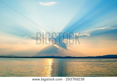 Sea sunset landscape with dramatic sunset sky - sea water surface lit by sunset summer sky light. Summer sunny water scene with colorful sky. Sea summer nature with mountain range at the sky horizon