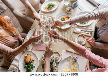 Clink Glasses. Five Women. Portrait Of Young People Having Breakfast At Table In Restaurant. Champag