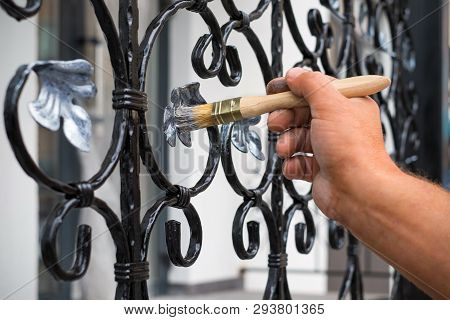 Contractor Hand With Brush That Painting Metal Fence.