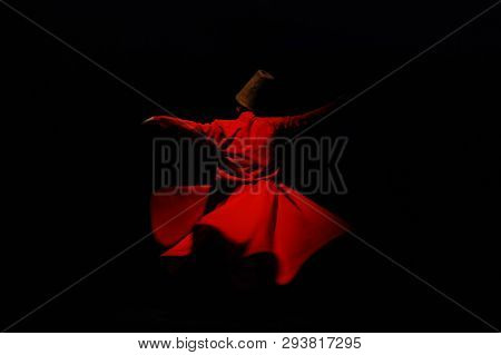 Whirling dervish in red garment on black background poster