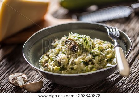 Italian Risotto Zucchini Mushrooms And Parmesan In Dark Plate.
