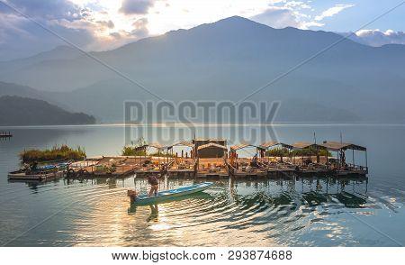 A-man-starts-a-motor-in-a-fishing-motor-boat In Sunrise Morning At Sun Moon Lake ,taiwan