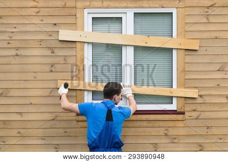 A Man In Coveralls Closes The Windows With Boards To Protect The House During A Long Departure And H