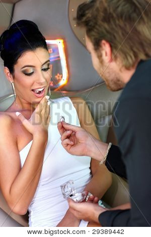 Happy woman receiving engagement ring from young man.?