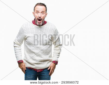 Middle age hoary senior man wearing winter sweater over isolated background afraid and shocked with surprise expression, fear and excited face.