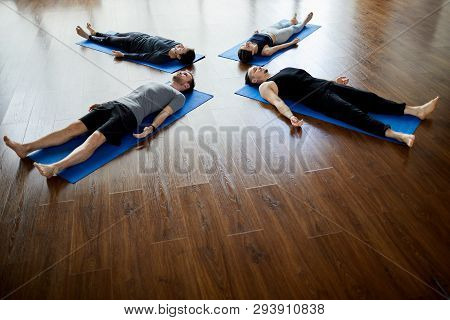 Group Of Relaxed Young People Lying On Mats In Circle And Doing Savasana While Napping At End Of Yog