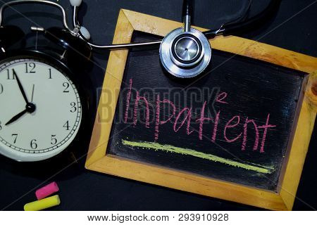 The Words Inpatient Handwriting On Chalkboard On Top View. Alarm Clock, Stethoscope On Black Backgro